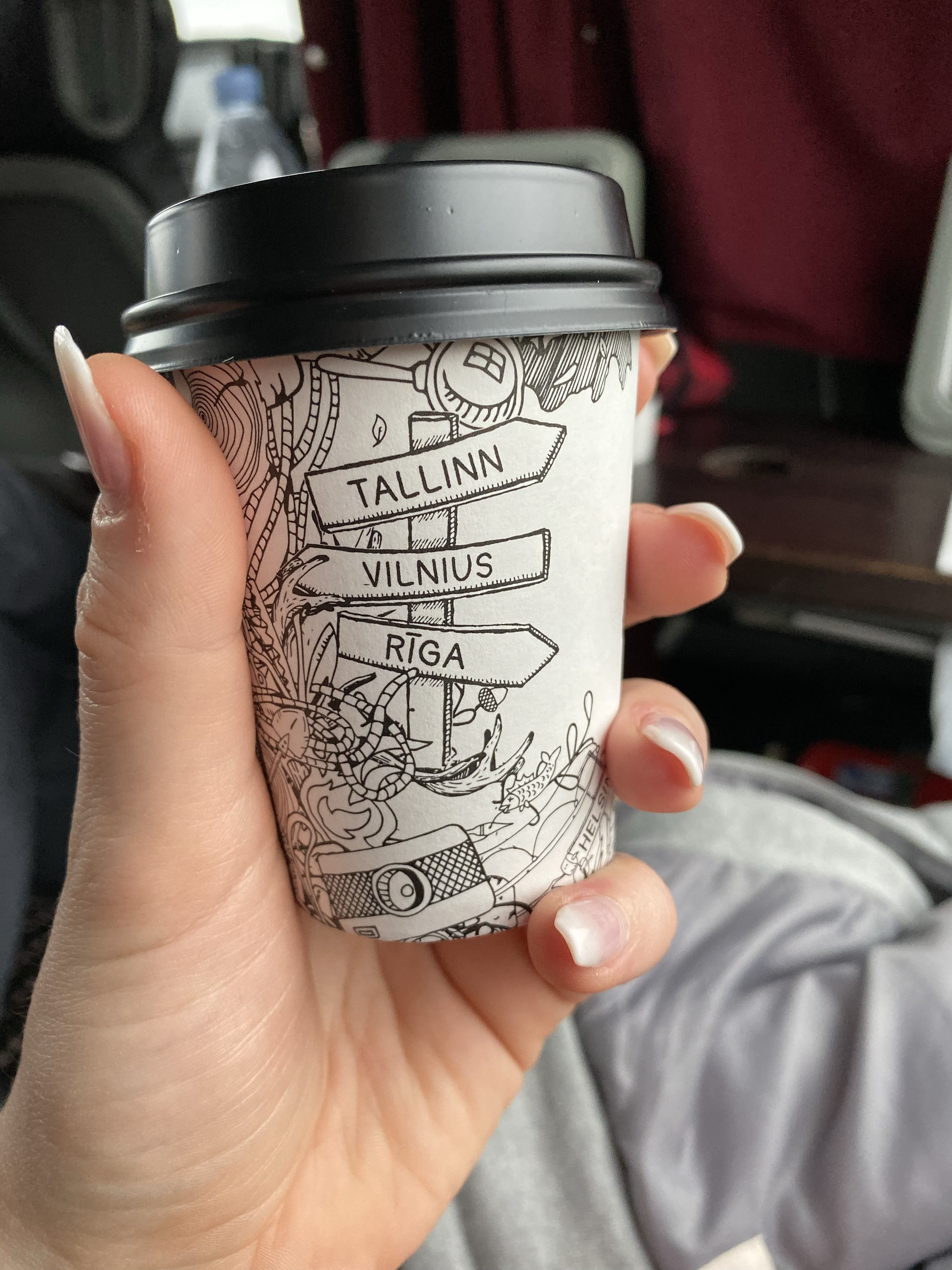 A coffee cup with directional signs for Tallinn, Vilnius and Riga on it.