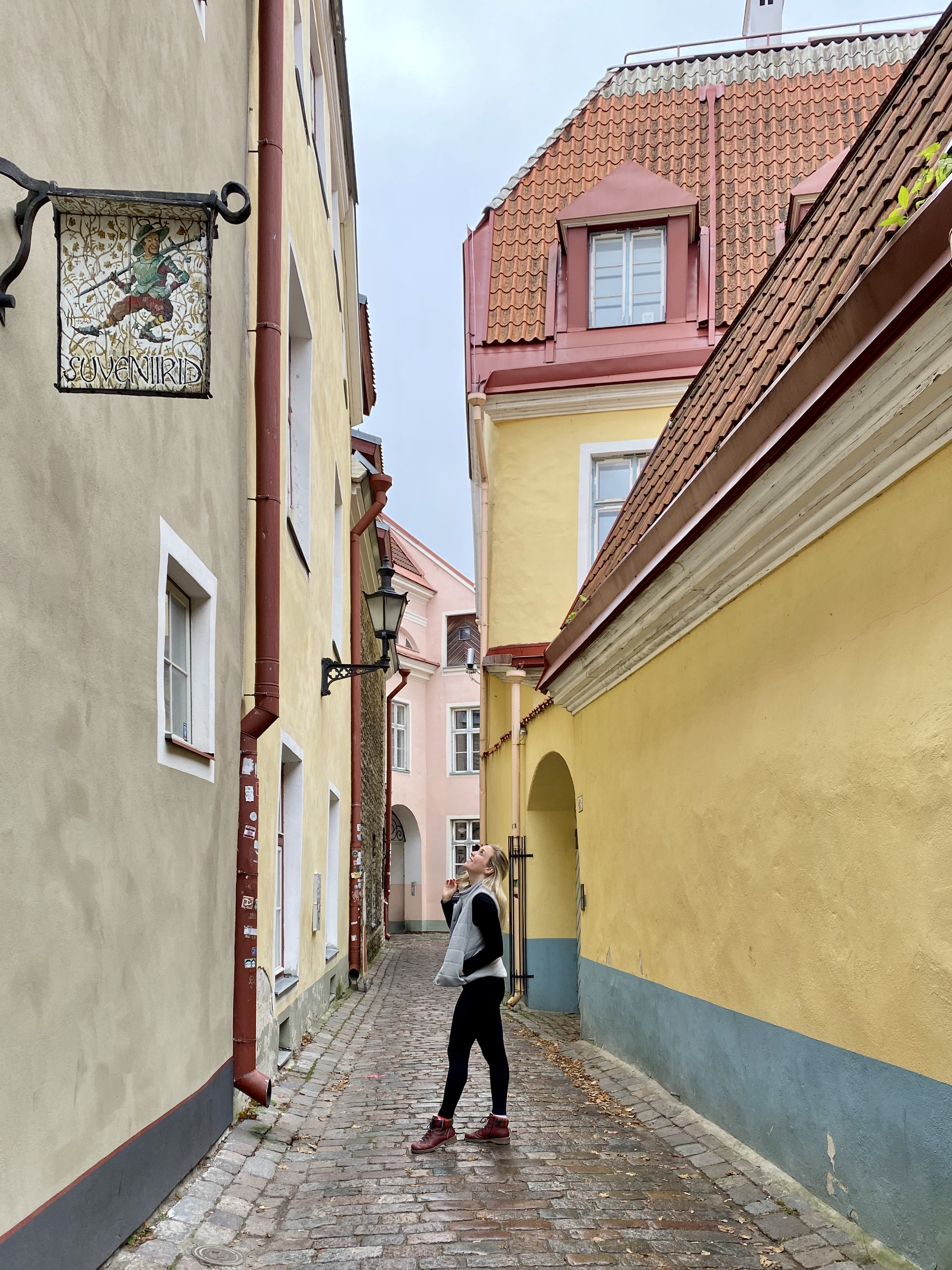 Erinn standing in an alley with colorful walls in Tallinn, Estonia.