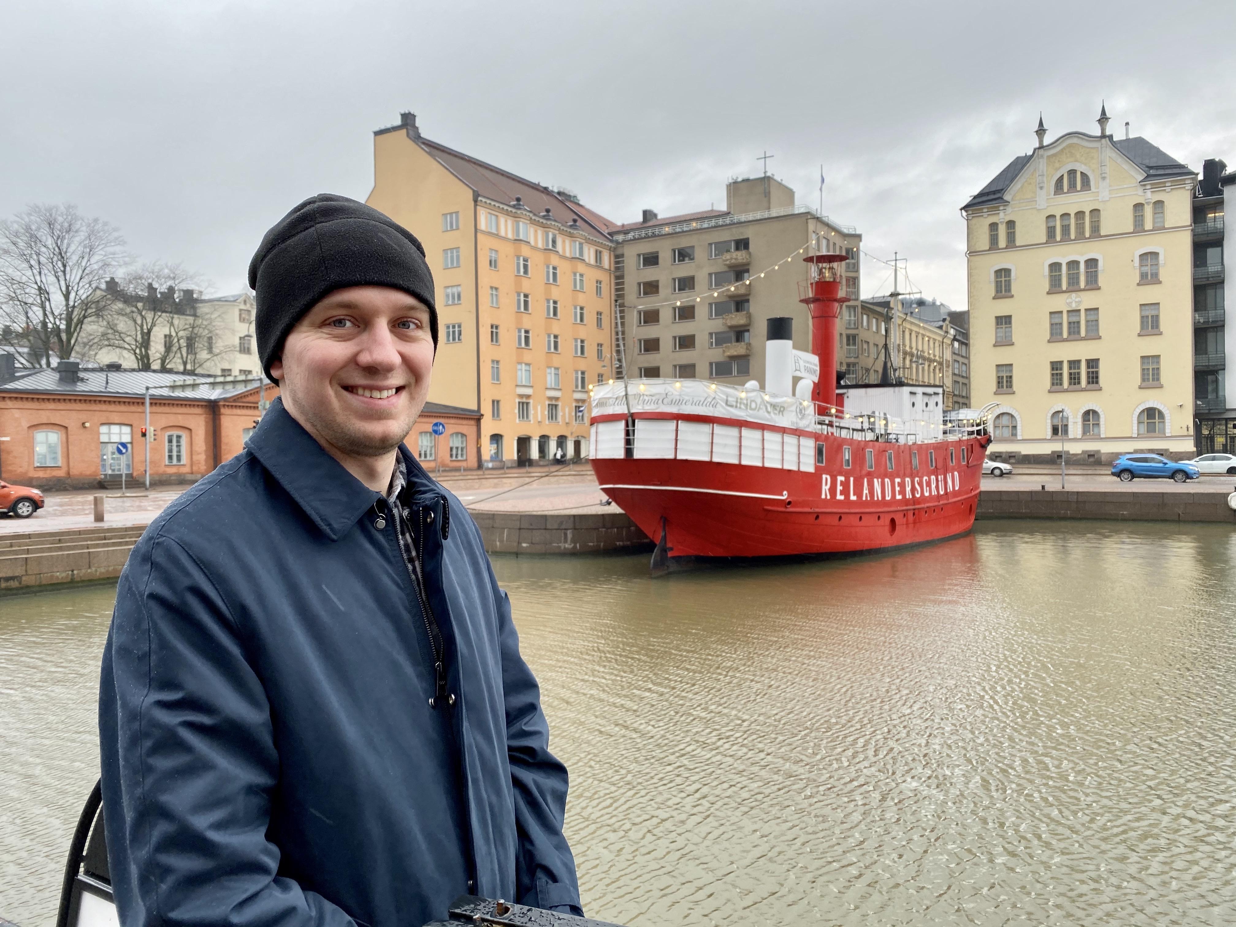 Ben in front of a red boat in Helsinki, Finland.