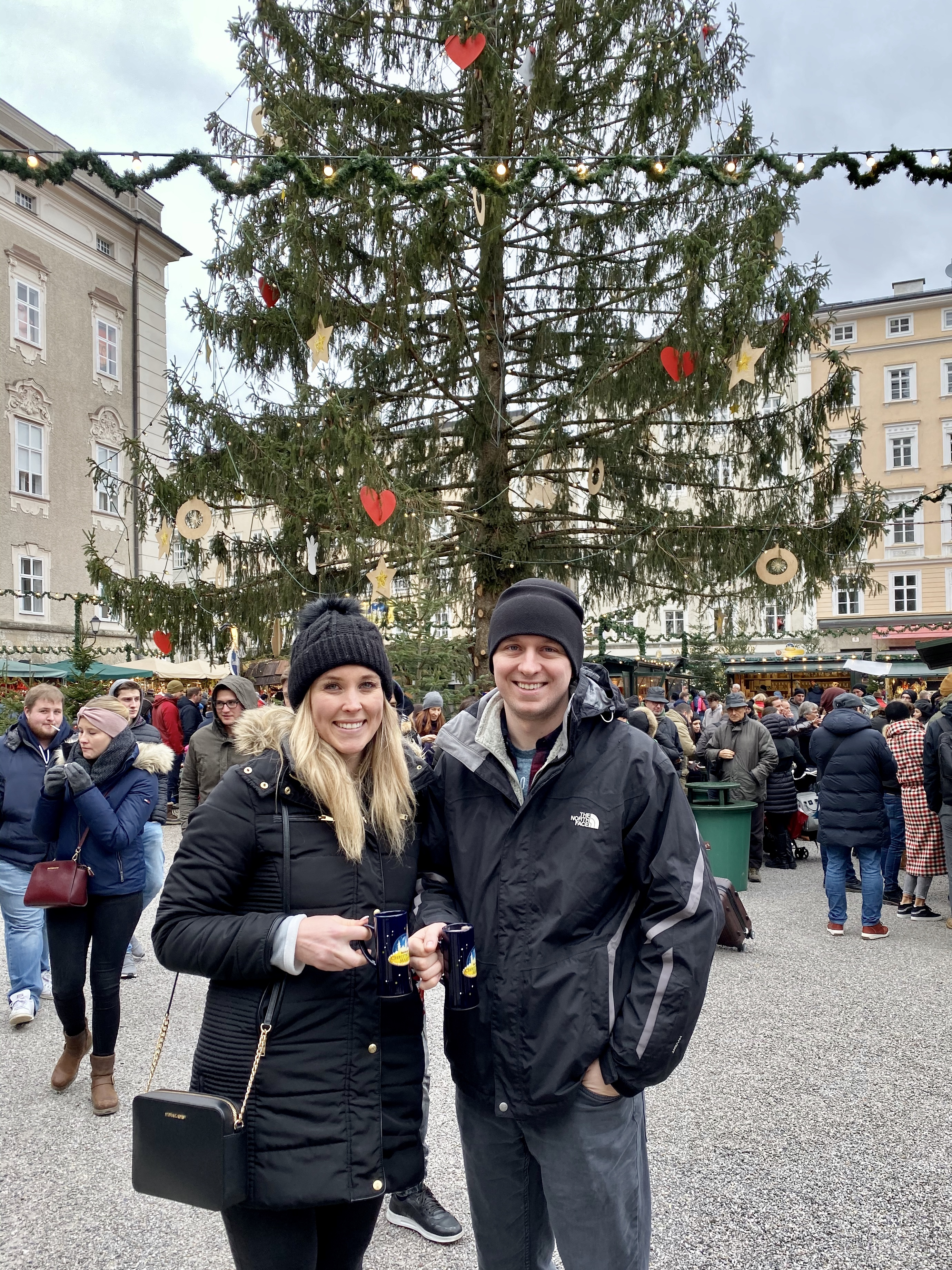 Erinn and Ben in front of a Christmas tree at Salzburg Christmas Market.