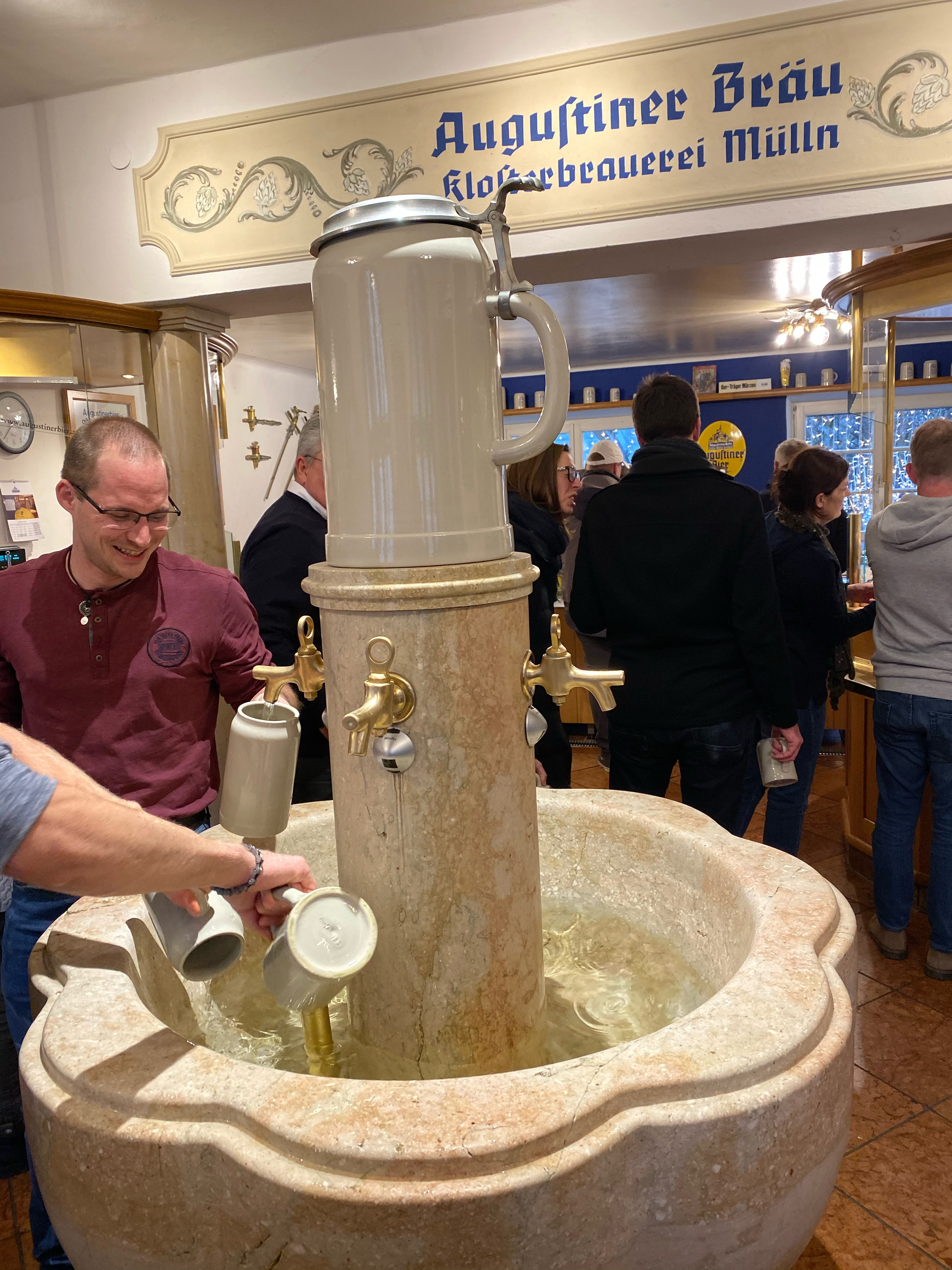 People rinsing cups with water before filling them with beer at Augustiner Bräu Kloster Mülln.